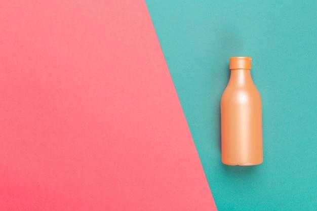 Produto cosmético em um fundo bicolor brilhante, vista superior