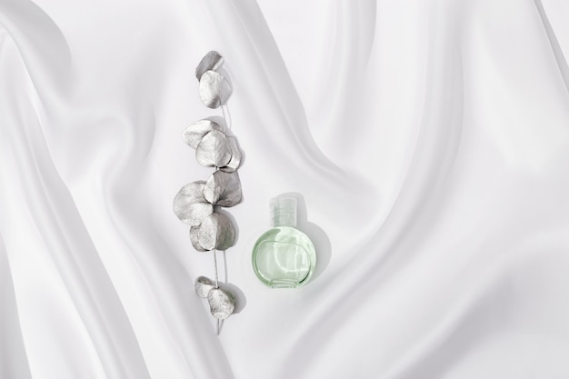 Produto cosmético, gel transparente ou creme para o corpo com ramo de eucalipto pintado na cor prata sobre pano de seda branco