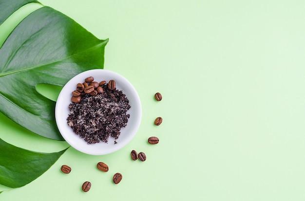 Produto cosmético natural para o cuidado da pele. folha monstera e esfrega com café moído e grãos para massagem, esfoliação