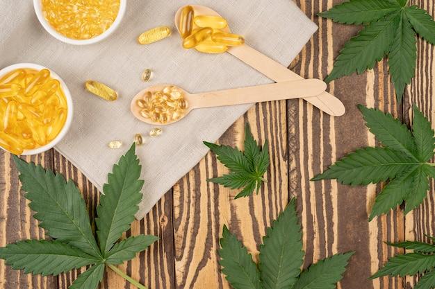Produto de cannabis para a saúde óleo de cannabis e pílulas com folhas de cannabis frescas vista superior cópia do espaço