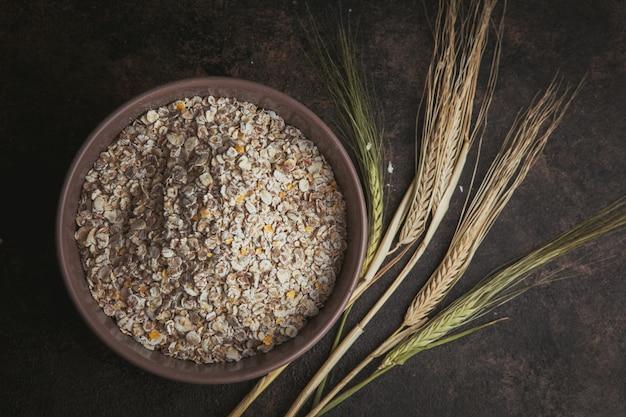 Produto de cereais em uma tigela com vista superior do trigo em um marrom escuro