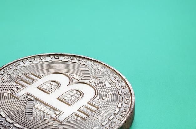 Produto de chocolate sob a forma de bitcoin física encontra-se sobre um fundo de plástico verde. modelo da moeda criptografada na forma comestível