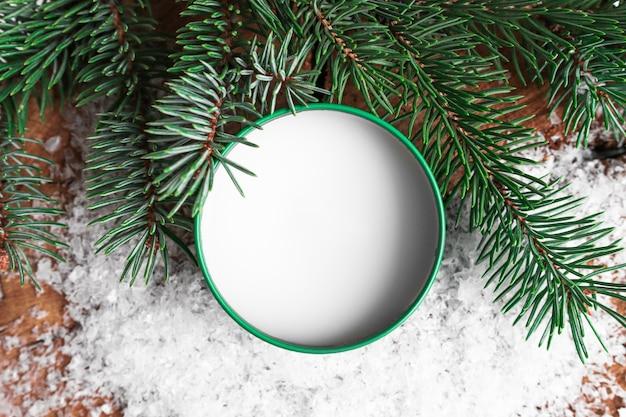 Produto de cuidado corporal em um fundo de neve com creme de ramos de abeto verde em uma vista superior do frasco verde