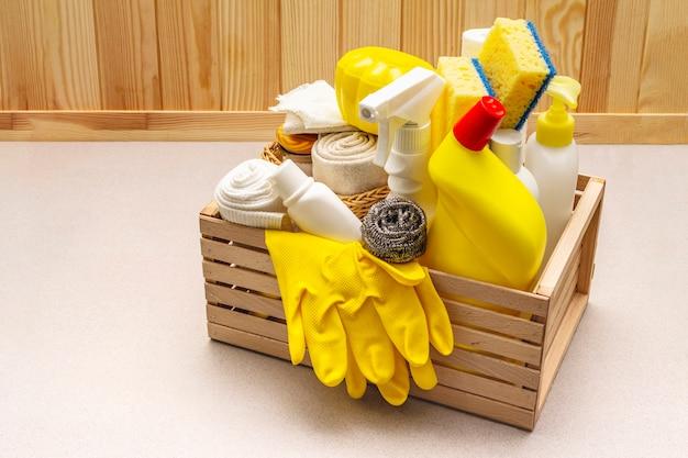 Produto de limpeza da casa em caixa de madeira. spray, garrafa, luvas, esponja de lavar louça, raspador, purificador de ar em gel.