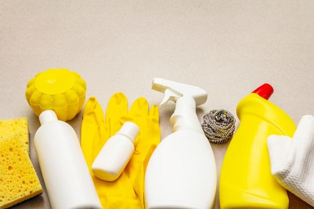 Produto de limpeza da casa no fundo concreto de pedra. spray, garrafa, luvas, esponja de lavar louça, raspador, refrogerador de ar em gel