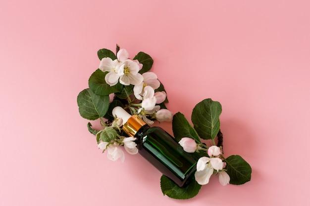 Produto de óleo essencial natural caseiro para a pele. flores de maçã rosa e frasco de vidro cosmético com conta-gotas para soro hidratante, tônico facial, limpeza, removedor de maquiagem ou tratamento de acne.