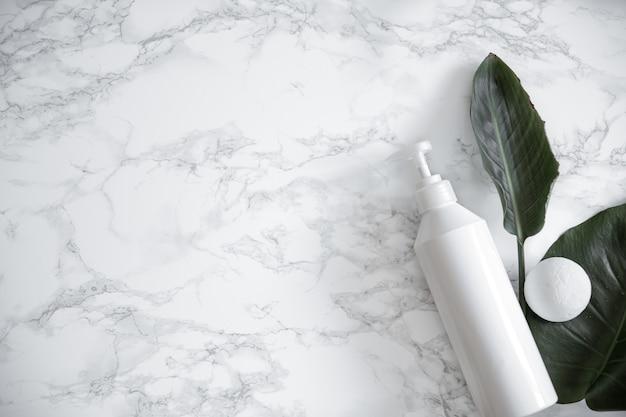 Produto de tratamento e folhas naturais sobre superfície de mármore