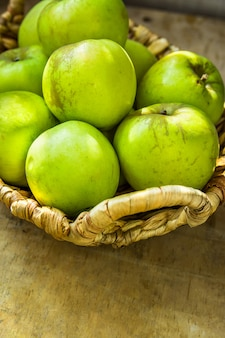 Produto local orgânico maduro verde das maçãs bio na cesta de vime do vintage na tabela de madeira