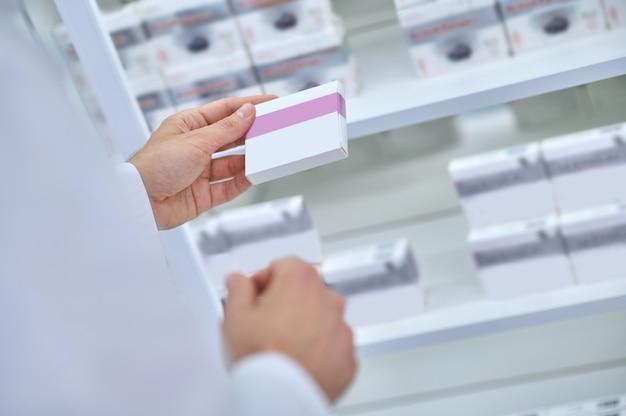 Produto medicinal. mãos de um homem de jaleco branco segurando um pacote de medicamento no saguão iluminado da farmácia, rosto não visível