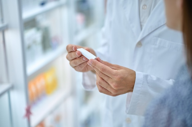 Produto médico. consultor farmacêutico com as mãos de jaleco branco segurando um pequeno tubo mostrando o visitante na farmácia, o rosto não está visível