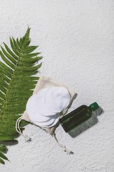 Produto natural para o cuidado da pele em frasco de vidro com conta-gotas com folhas verdes no fundo do concerto