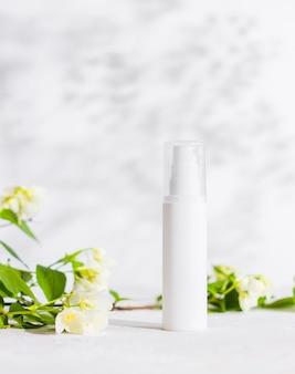 Produto para a pele em uma garrafa de plástico com flores de jasmim