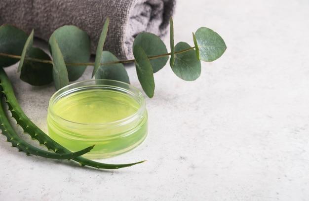 Produto para a pele, gel de aloe vera em pote e folhas de eucalipto na mesa
