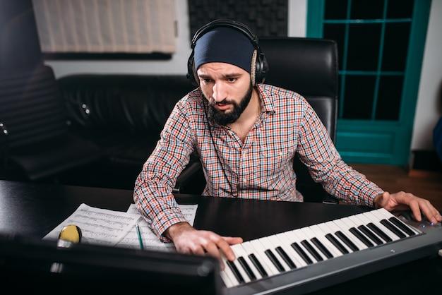 Produtor de som em fones de ouvido trabalha com teclado musical em estúdio. tecnologia de gravação de áudio digital profissional