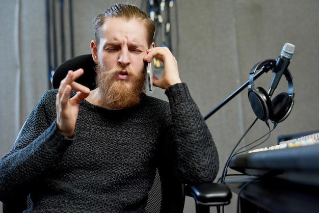 Produtor de som falando ao telefone no estúdio