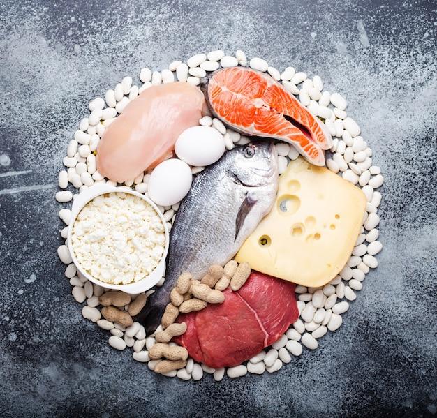 Produtos alimentares para uma dieta cetogênica equilibrada com baixo teor de carboidratos: peixe, carne, frango, ovos, laticínios, feijão, queijo, nozes em fundo cinza conceito de produtos keto para dieta e perda de peso, vista de cima, close-up