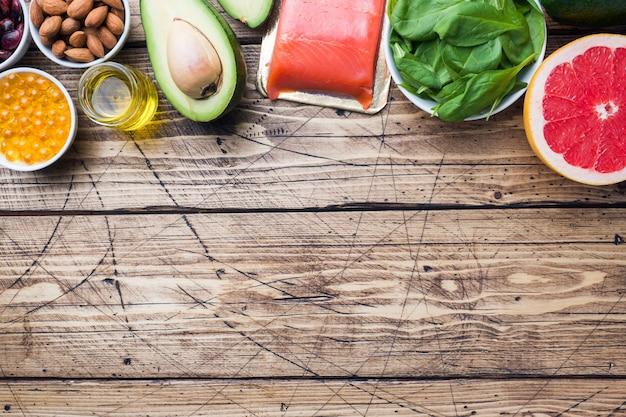 Produtos antioxidantes do alimento saudável do conceito: peixes e óleo do abacate, das porcas e de peixes, toranja no fundo de madeira. espaço da cópia