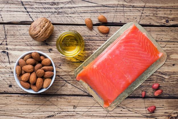 Produtos antioxidantes do alimento saudável do conceito: porcas e óleo dos peixes no fundo de madeira.
