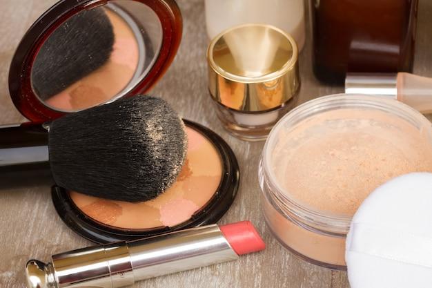 Produtos básicos de maquiagem - base, pó e batom, close-up