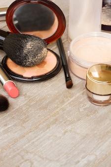 Produtos básicos de maquiagem - base, pó e batom em fundo de madeira com espaço de cópia