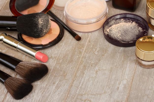 Produtos básicos de maquiagem - base, pó e batom na mesa cinza com espaço de cópia
