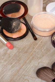 Produtos básicos de maquiagem - base, pó e batom na mesa de madeira cinza com espaço para cópia