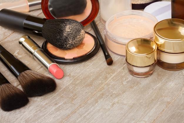 Produtos básicos de maquiagem - base, pó e batom na mesa de madeira com espaço de cópia