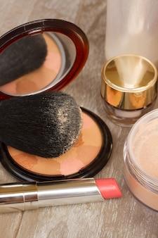 Produtos básicos de maquiagem de perto - base, pó e batom rosa