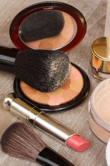 Produtos básicos de maquiagem em close - base, pó e batom