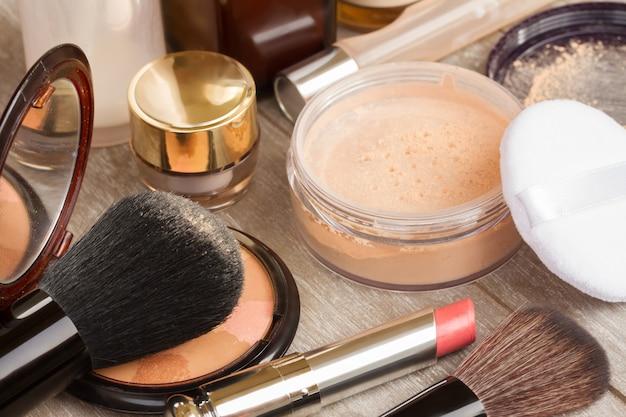 Produtos básicos de maquiagem na mesa - base, pó e batom
