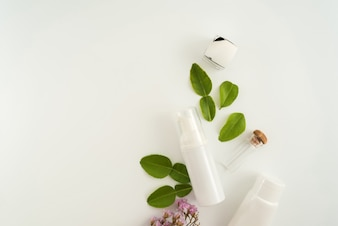 Produtos cosméticos brancos e folhas verdes sobre fundo branco. Conceito de maquete de marca.