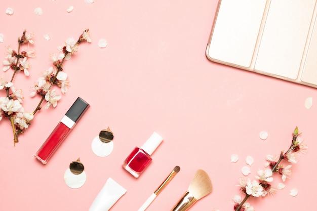 Produtos cosméticos, brincos, bolsa em um fundo rosa. vista plana leiga