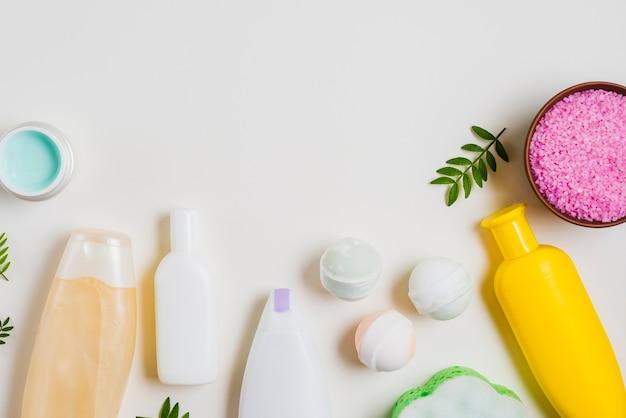 Produtos cosméticos com bomba de banho; sal rosa e creme em pano de fundo branco