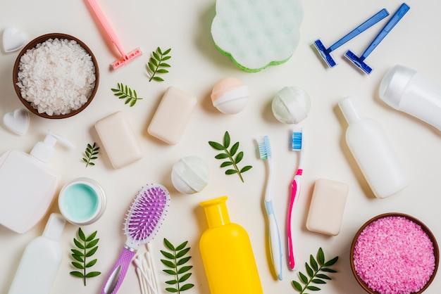 Produtos cosméticos com sal; escova dental; navalha; escova de cabelo e folhas no pano de fundo branco