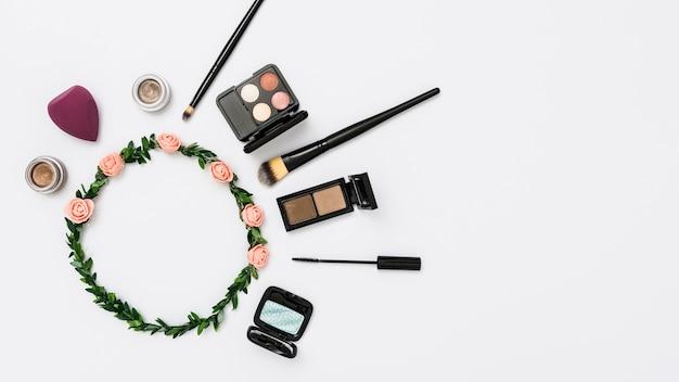 Produtos cosméticos com tiara rosa e folhas, isolado no fundo branco