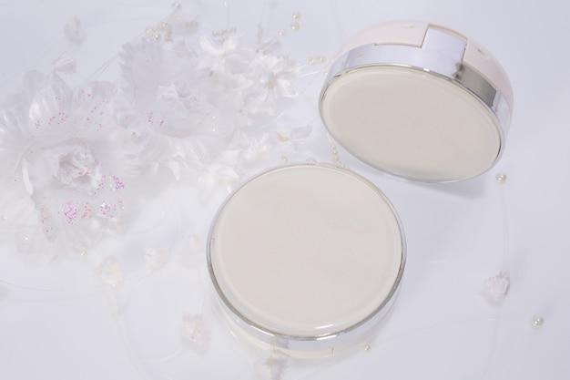 Produtos cosméticos e flores em branco
