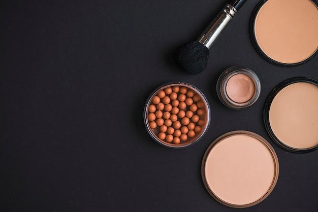 Produtos cosméticos e pincel de maquiagem em pano de fundo preto
