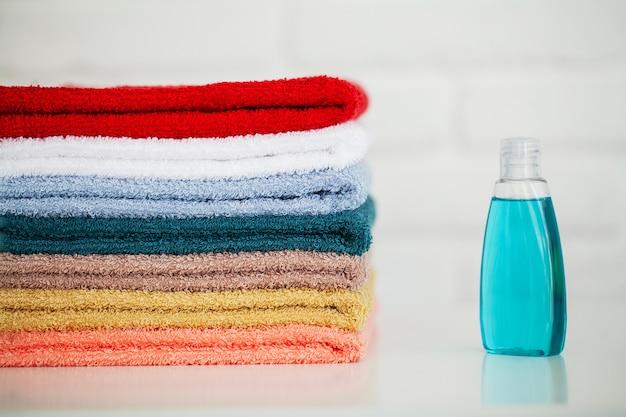 Produtos cosméticos e toalhas de algodão na mesa de madeira branca no salão de beleza