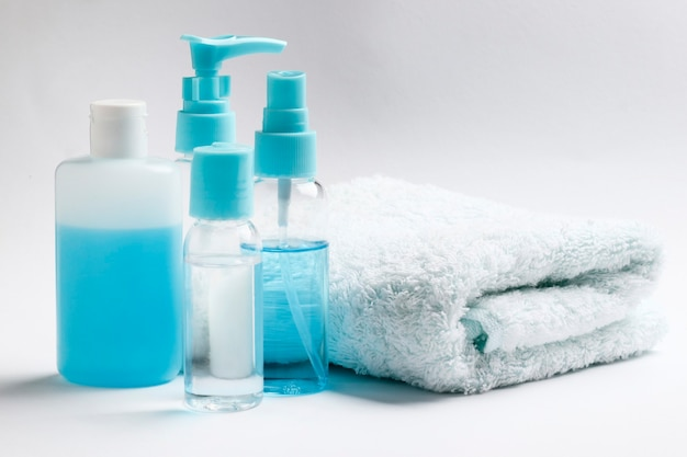 Produtos cosméticos e uma toalha em um fundo branco