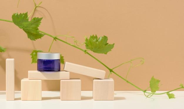 Produtos cosméticos em frasco de vidro azul com tampa cinza sobre pódio de madeira feito de cubos, atrás de um ramo de uvas com folhas verdes. em branco para produtos de marca, hidratante em fundo bege