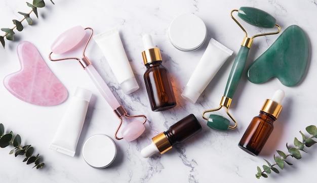 Produtos cosméticos, óleos essenciais, tubos de creme e rolo facial em uma mesa de mármore