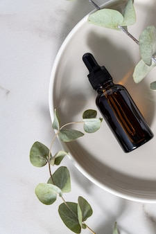 Produtos cosméticos para a pele em conta-gotas de vidro escuro com eucalipto em fundo claro. postura plana, copie o espaço