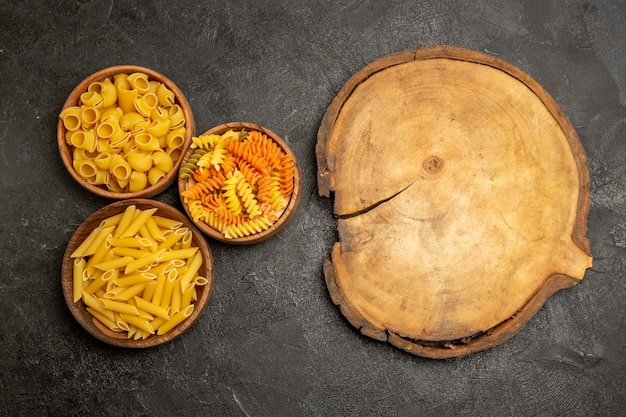 Produtos crus de composição de massa de vista superior dentro de pratos em uma mesa cinza
