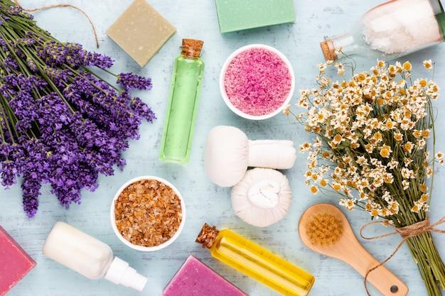 Produtos de aliciamento e buquê de lavanda fresca na mesa de madeira branca.