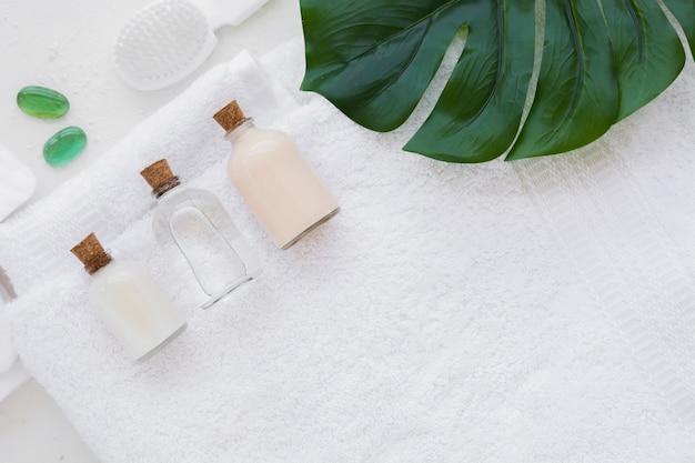 Produtos de banho na toalha com almofadas de algodão e folhas