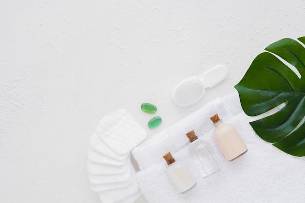 Produtos de banho na toalha com almofadas de algodão, folha e cópia espaço