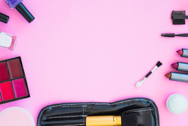 Produtos de beleza cosméticos dispostos em fundo rosa com espaço vazio para texto