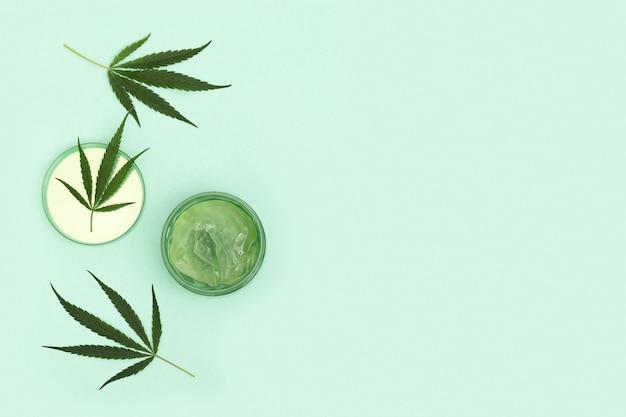 Produtos de beleza de cannabis que contêm ingredientes naturais de origem vegetal pote de creme de cânhamo e folha verde