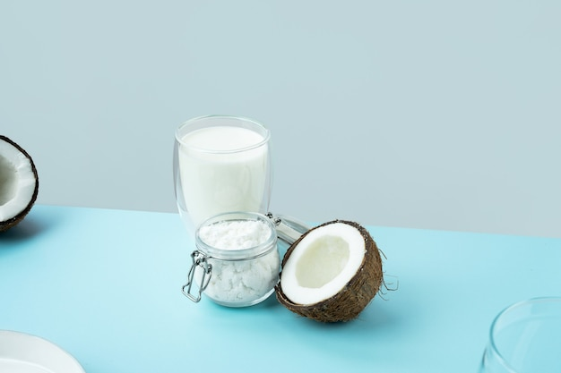 Produtos de coco quebrados coco aberto com carne cortada ao meio coco em pó em um frasco de vidro vegetal leite