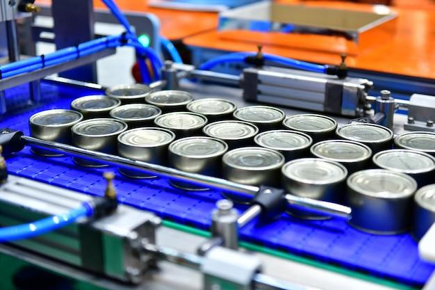 Produtos de conservas alimentares na correia transportadora no armazém de distribuição conceito de sistema do transporte das espigas.